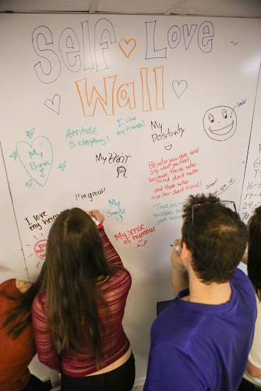 "Students drawing on a whiteboard that reads ""Self Love Wall"" with hearts and smiles and various quotes throughout."